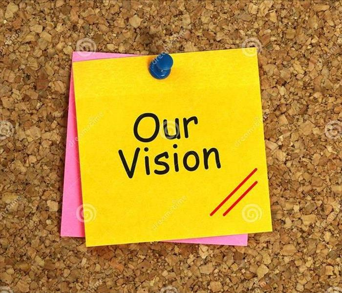 "Sticky note with ""Our Vision"" pinned on a cork board."