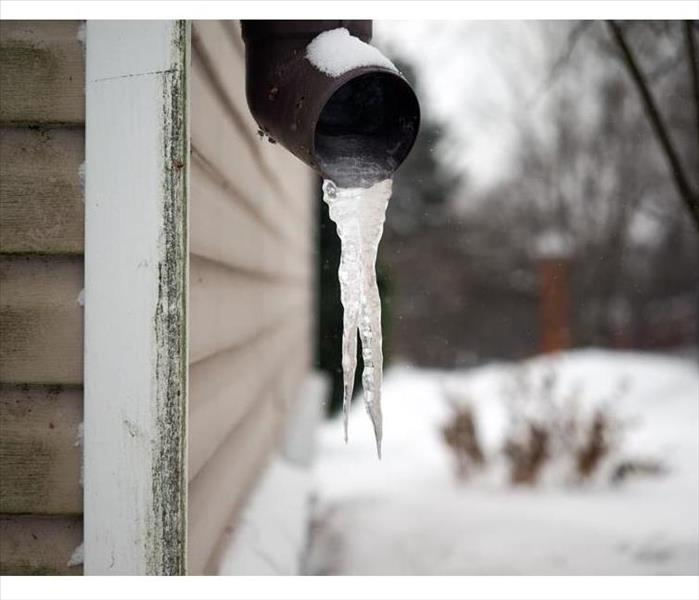 Frozen water pouring from pipe