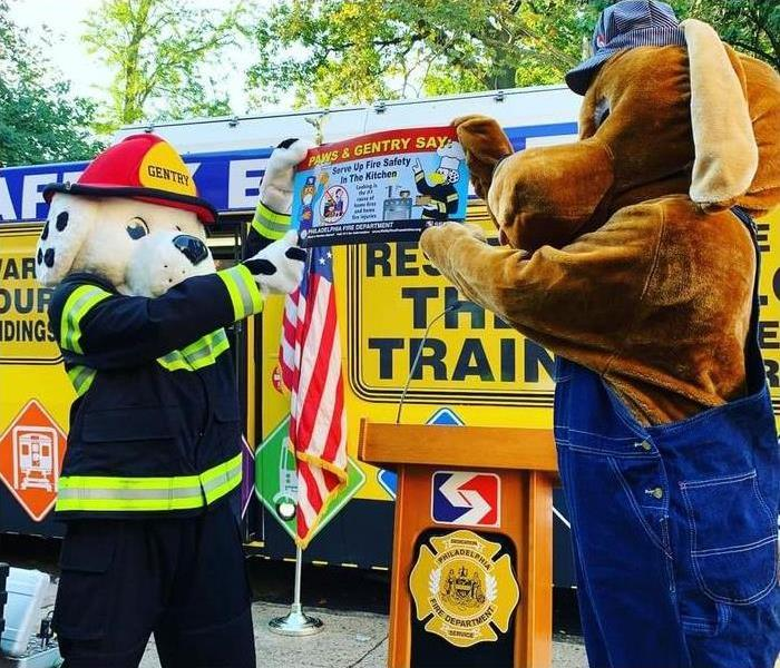 Dalmation dressed as fire fighter and other dog holding up a sign with the Fire Prevention Week campaign photo